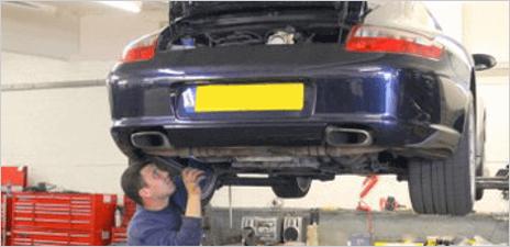 A mechanic working on a raised car