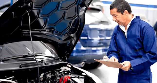 Mechanic looking under car bonnet